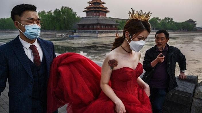A Chinese man carries his future bride's dress while taking pictures in advance of their wedding in Beijing.