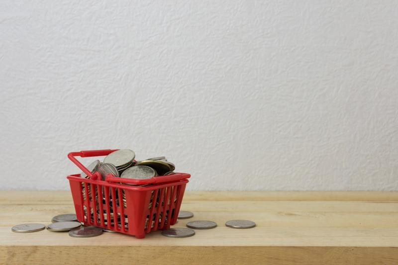 Coins sitting in a grocery basket.