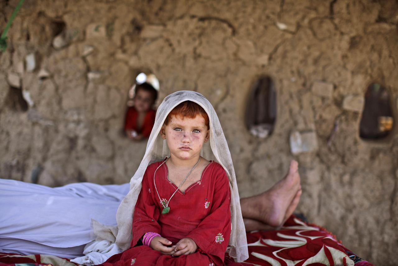 In this Tuesday, Aug. 7, 2012, Afghan refugee girl, laiba Hazrat, 5, sits on a bed next to her sleeping granfather, outside their home in a slum on the outskirts of Islamabad, Pakistan. Hundreds of thousands of Afghan refugees are in limbo as Pakistan, increasingly frustrated with hosting the world's largest and longest-running refugee population, weighs whether to renew their refugee status by the end of this year. A large-scale return of the 1.7 million Afghan refugees currently living in Pakistan would be a massive problem for Afghanistan at a time when it's already struggling to maintain security in the face of an American troop withdrawal. But Pakistan increasingly seems to be angry at a refugee population that many feel has overstayed its welcome. (AP Photo/Muhammed Muheisen)
