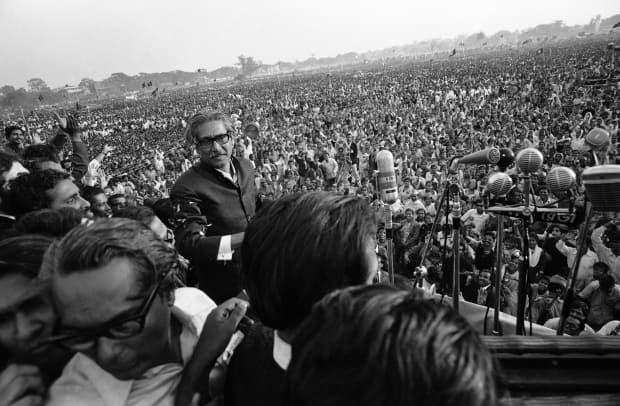 On Jan. 11, 1972, nationalist leader Sheikh Mujibur Rahman walks towards a battery of microphones to address an estimated one million people at a rally in the race course ground of Dacca, Bangladesh.