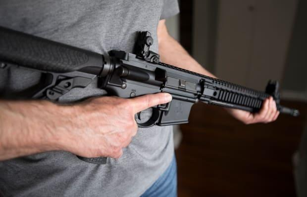 A restricted gun license holder holds a AR-15 at his home in Langley, B.C., on May 1, 2020. (Jonathan Hayward/The Canadian Press - image credit)