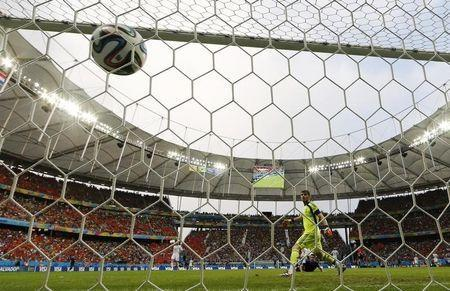 Robin van Persie of the Netherlands (bottom) heads to score past Spain's Iker Casillas during their 2014 World Cup Group B soccer match at the Fonte Nova arena in Salvador June 13, 2014. REUTERS/Michael Dalder