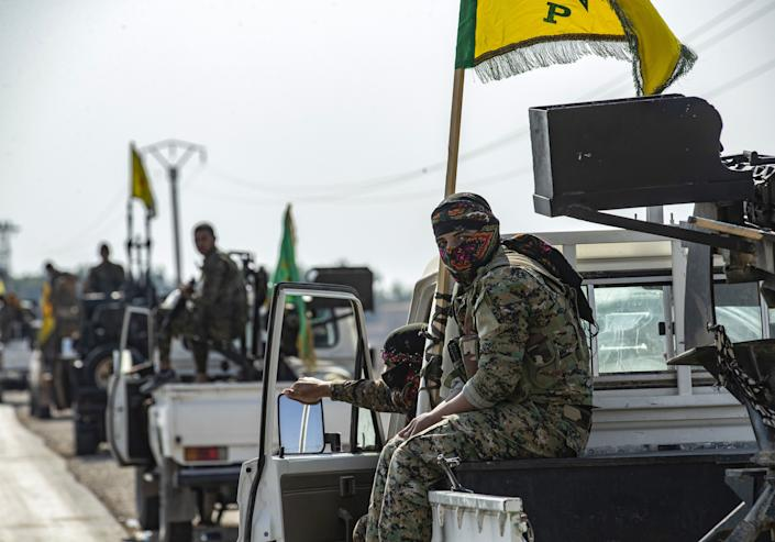Fighters from the Syrian Democratic Forces ((SDF)) gather in their military vehicles as they withdraw from the Sanjak Saadoun border area near the northern Syrian town of Amuda, on October 27, 2019.  (Photo by Delil Souleiman/AFP via Getty Images)