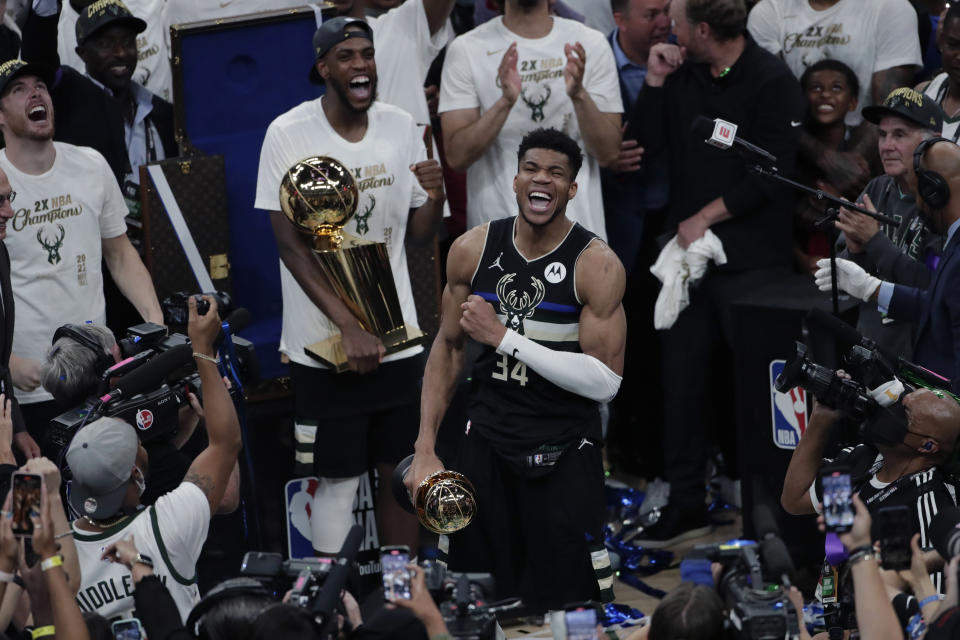 Milwaukee Bucks forward Giannis Antetokounmpo celebrates with the MVP trophy, as teammates hold the championship trophy, after defeating the Phoenix Suns in Game 6 of basketball's NBA Finals Tuesday, July 20, 2021, in Milwaukee. (AP Photo/Aaron Gash)