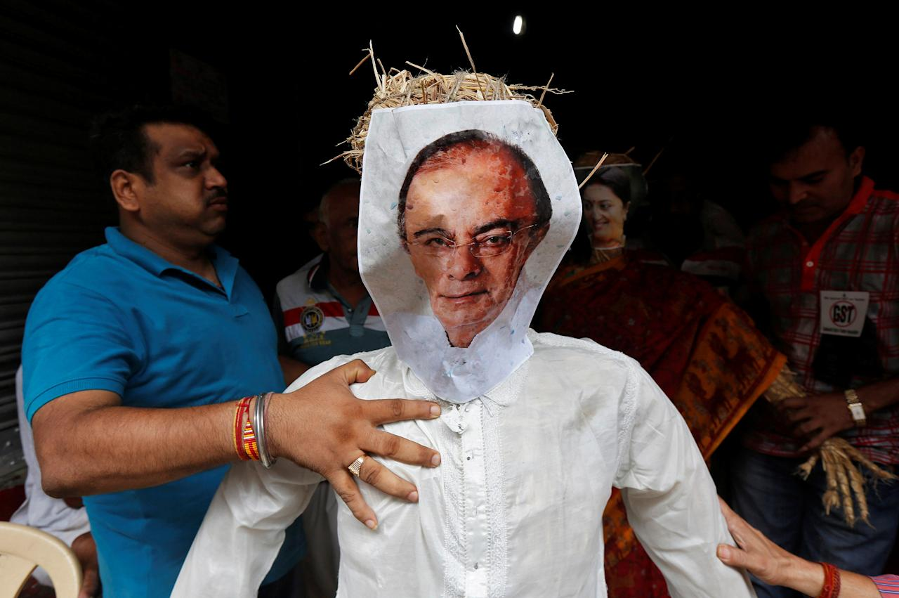 Cloth merchants hold an effigy depicting India's Finance Minister Arun Jaitley before burning it at a protest against the implementation of the Goods and Services Tax (GST) on textiles, in Kolkata, India June 29, 2017. REUTERS/Rupak De Chowdhuri