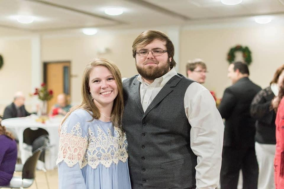 Haley Richardson, wearing a blue smock dress and her husband Jordan, wearing a suit and tie, dressed up at an important function  Source: Facebook