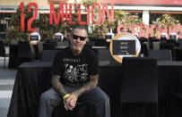 Mike Ness of the rock band Social Distortion sits at one of the 48 empty tables set up at the ONE VOICE event, in honor of the live events industry which has been devastated by the COVID-19 pandemic, Wednesday, Aug. 12, 2020, at L.A. Live in Los Angeles. (AP Photo/Chris Pizzello)