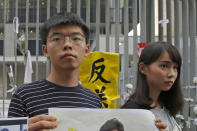 FILE - In this June 18, 2019, file photo, pro-democracy activists Agnes Chow, right, and Joshua Wong speak to the media outside government office in Hong Kong. Demosisto, a pro-democracy group in Hong Kong posted on its social media accounts that well-known activist Joshua Wong had been pushed into a private car around 7:30 a.m. Friday, Aug. 30, 2019 and was taken to police headquarters. It later said another member, Agnes Chow, had been arrested as well. (AP Photo/Kin Cheung, File)