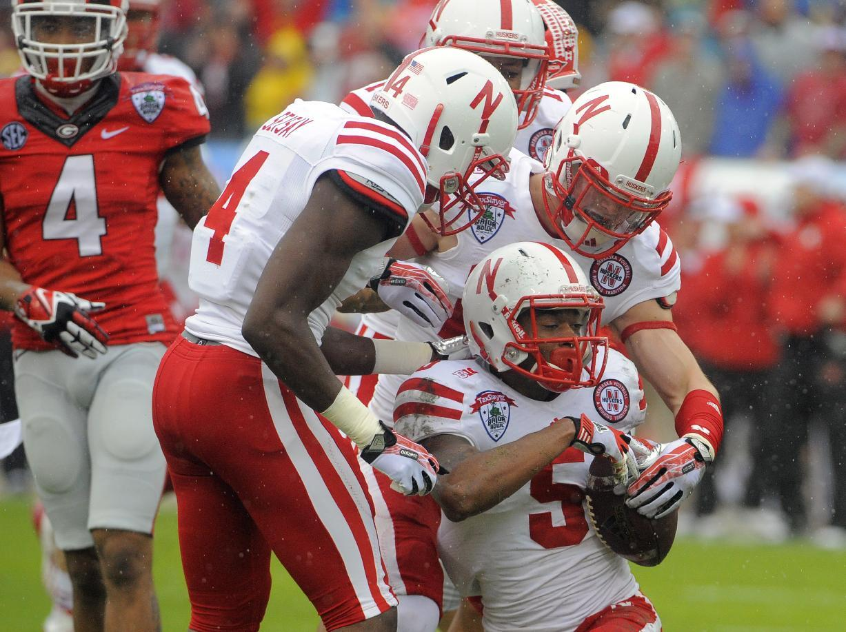 Nebraska cornerback Josh Mitchell (5) celebrates with his teammates after recovering a fumbled kick return during the first half of the Gator Bowl NCAA college football game against Georgia, Wednesday, Jan. 1, 2014, in Jacksonville, Fla. (AP Photo/Stephen B. Morton)