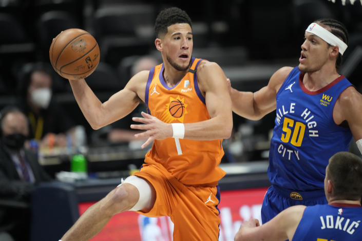 Phoenix Suns guard Devin Booker, left, passes the ball as Denver Nuggets forward Aaron Gordon defends during the first half of Game 3 of an NBA second-round playoff series Friday, June 11, 2021, in Denver. (AP Photo/David Zalubowski)