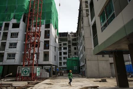 A migrant worker walks in a construction site for buildings, in Bangkok