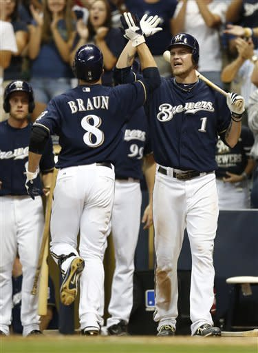Milwaukee Brewers' Ryan Braun (8) gets a high-five from teammate Corey Hart (1) after Braun's home run against the Pittsburgh Pirates during the sixth inning of a baseball game, Friday, July 13, 2012, in Milwaukee. (AP Photo/Jeffrey Phelps)