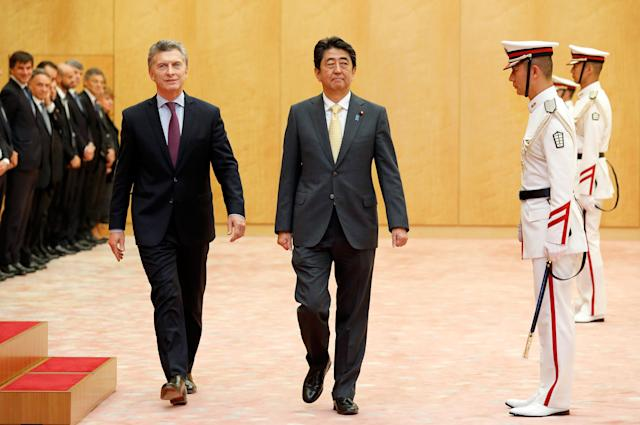 Argentina's President Macri is escorted by Japanese PM Abe after reviewing the guard of honor at Abe's official residence in Tokyo