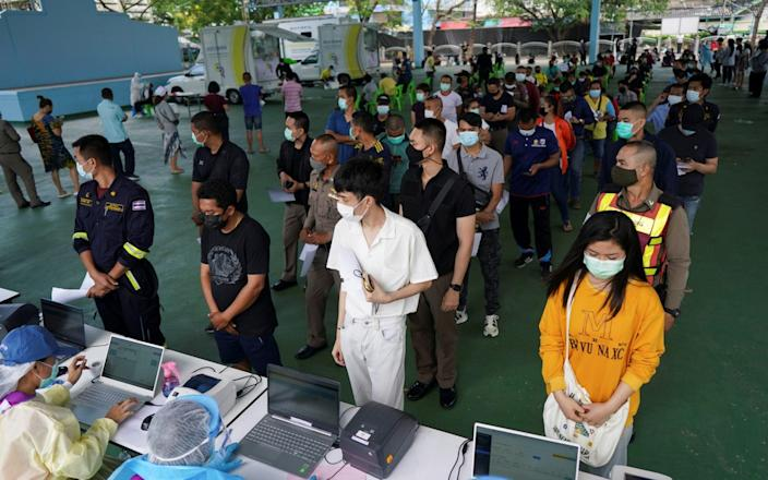 People queue to be tested for the coronavirus disease in Bangkok, as the country deals with a fresh wave of infections - ATHIT PERAWONGMETHA