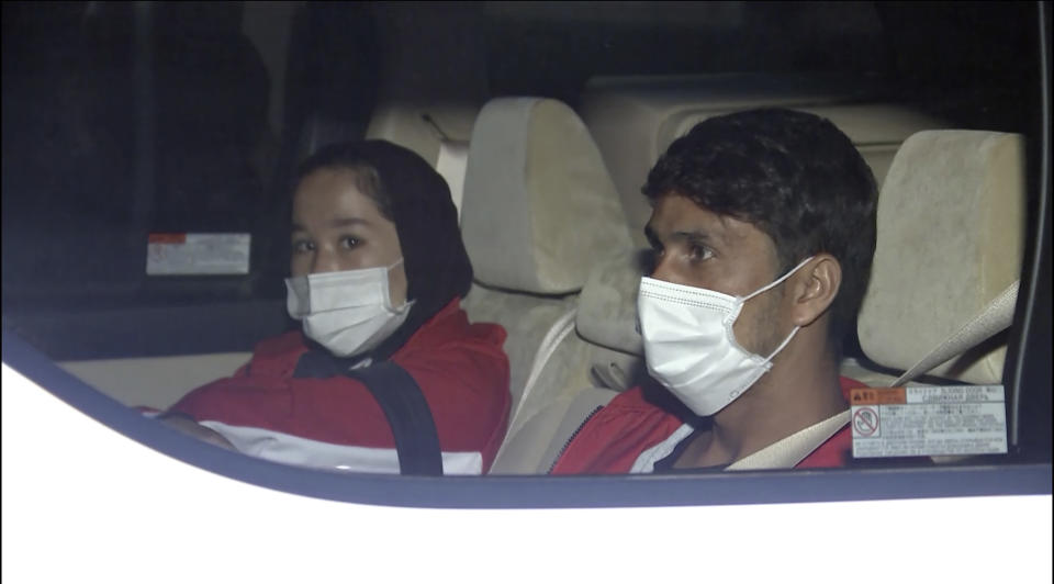 In this image made from a video, Afghan athletes Zakia Khudadadi, left, and Hossain Rasouli arrive at Haneda airport in Tokyo Saturday, Aug. 28, 2021. They have arrived in Tokyo, via what's been described as a harrowing journey from Kabul to Paris, to compete in the Paralympics. (TBS via AP)