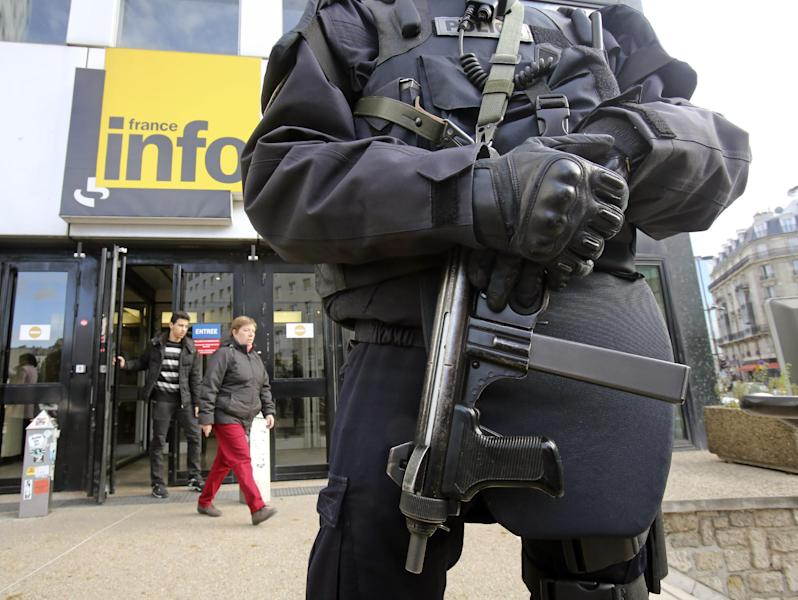 A French police officer wearing a bullet-proof jacket stands at the entrance of France Info radio station in Paris, Tuesday Nov. 19, 2013. French police are hunting for a gunman suspected in a shooting Monday at a Paris newspaper office that gravely wounded a photographer, as well as three other attacks around the nation's capital. The motive for the attacks, which prompted heightened security at media offices and the busy Champs-Elysees shopping avenue, is unclear.(AP Photo/Remy de la Mauviniere)