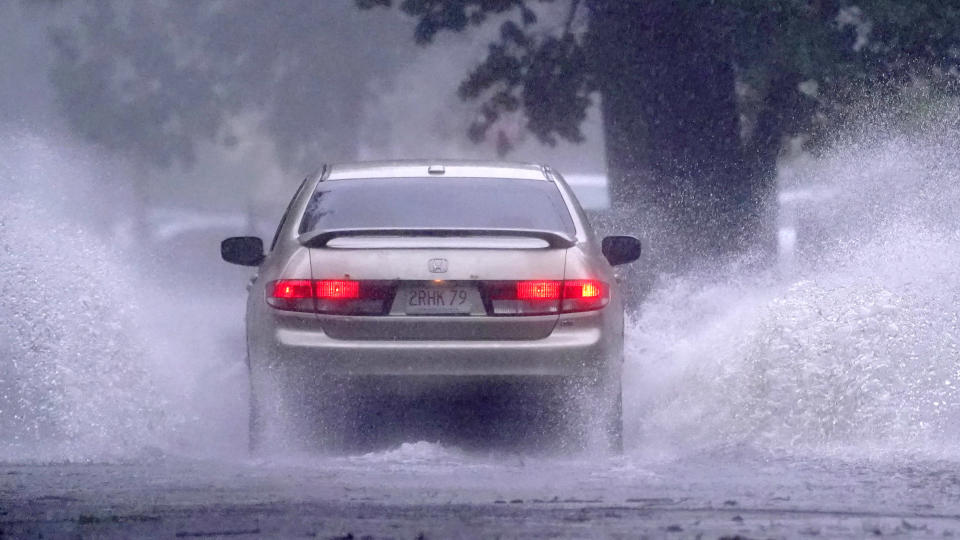 A car drives down a partially flooded street after the remnants of Hurricane Henri made landfall, Sunday, Aug. 22, 2021, in Springfield, Mass. (AP Photo/Charles Krupa)