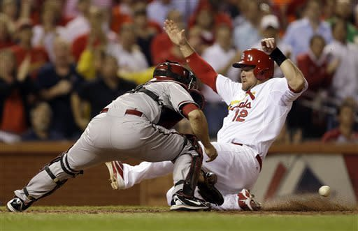 St. Louis Cardinals' Ty Wigginton, right, scores on a single by Carlos Beltran as Arizona Diamondbacks catcher Miguel Montero handles the throw during the seventh inning of a baseball game Tuesday, June 4, 2013, in St. Louis. (AP Photo/Jeff Roberson)
