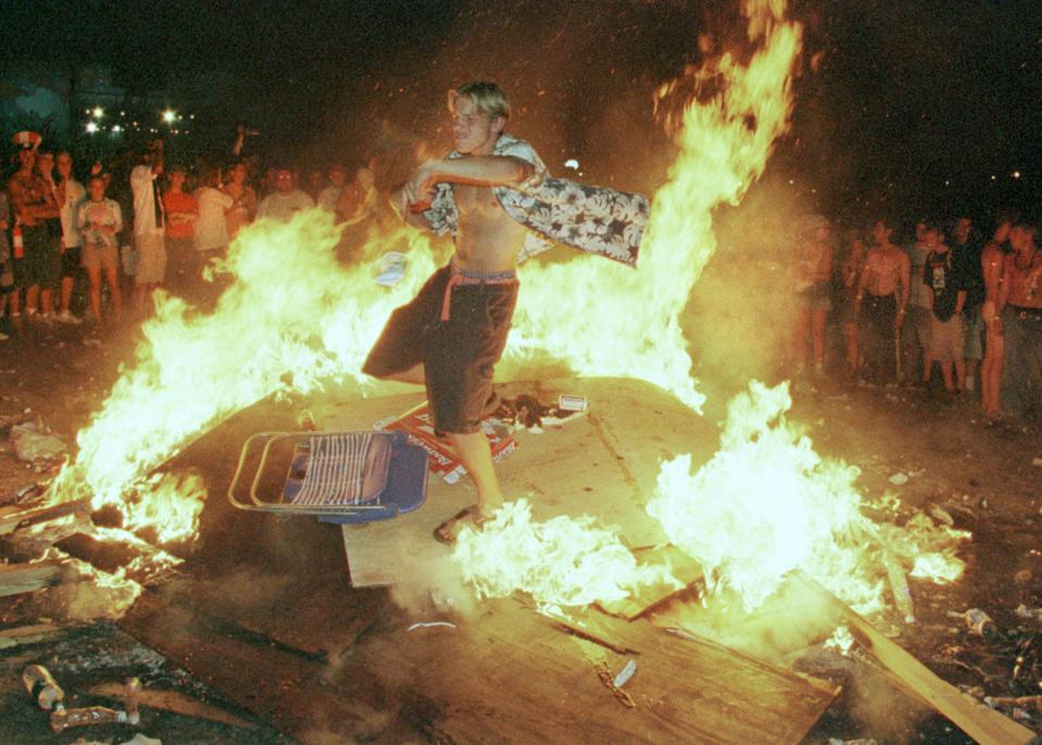 A young man dances in a fire created by plywood panels that had been he Woodstock Peace Wall. (Photo: Joe Traver/Getty Images)