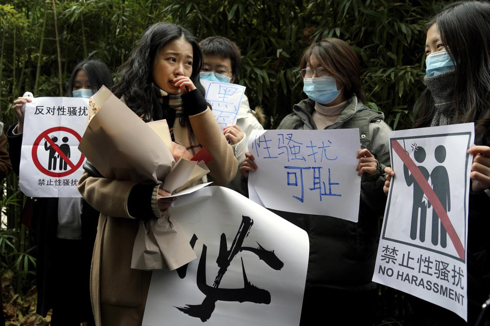 Zhou Xiaoxuan, second from left, walks by her supporters holding banners as she arrives at a courthouse in Beijing, Wednesday, Dec. 2, 2020. Zhou, a Chinese woman who filed a sexual harassment lawsuit against a TV host, told dozens of cheering supporters at a courthouse Wednesday she hopes her case will encourage other victims of gender violence in a system that gives them few options to pursue complaints. (AP Photo/Andy Wong)