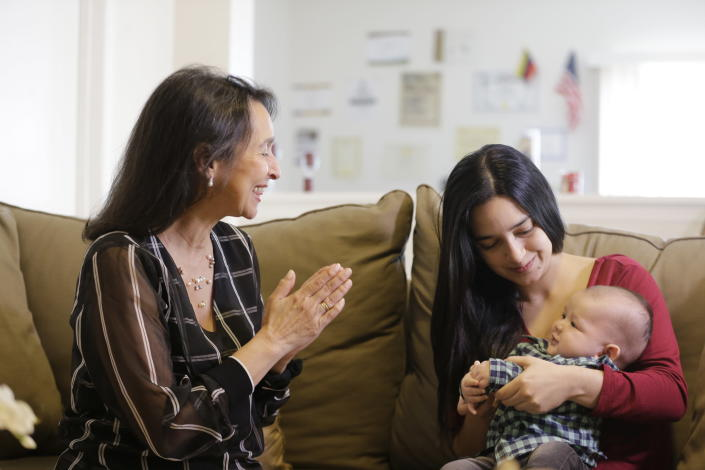 In this March 6, 2020 photo, Cioly Zambrano smiles at her three-month-old grandson held by his mother Maria Fernanda Rangel, in her home in Orlando, Florida. Zambrano, is one of 32 jurists named to the Supreme Court by opposition leader Juan Guaido, immediately converting her and her family into high-priority targets for arrest. Her son Jose Ramon Zambrano who is the baby's father and his wife Marisa Fernanda fled Venezuela the same day Nicolas Maduro's feared intelligence police raided his family's B&B. (AP Photo/Cody Jackson)