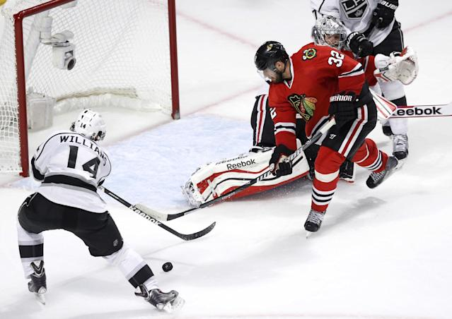 Chicago Blackhawks defenseman Michal Rozsival (32) keeps Los Angeles Kings right wing Justin Williams (14) from scoring during the second period of Game 1 of the Western Conference finals in the NHL hockey Stanley Cup playoffs in Chicago on Sunday, May 18, 2014. (AP Photo/Charles Rex Arbogast)