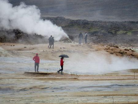 People look on as fumes come out of the ground near Reykjahlid, Iceland, September 19, 2015. Picture taken September 19, 2015. REUTERS/Lefteris Karagiannopoulos