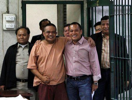 """Anti-government """"red shirt"""" leader Jatuporn poses with his colleague Nattawut before going to a court room at Thailand's Criminal Court in Bangkok"""