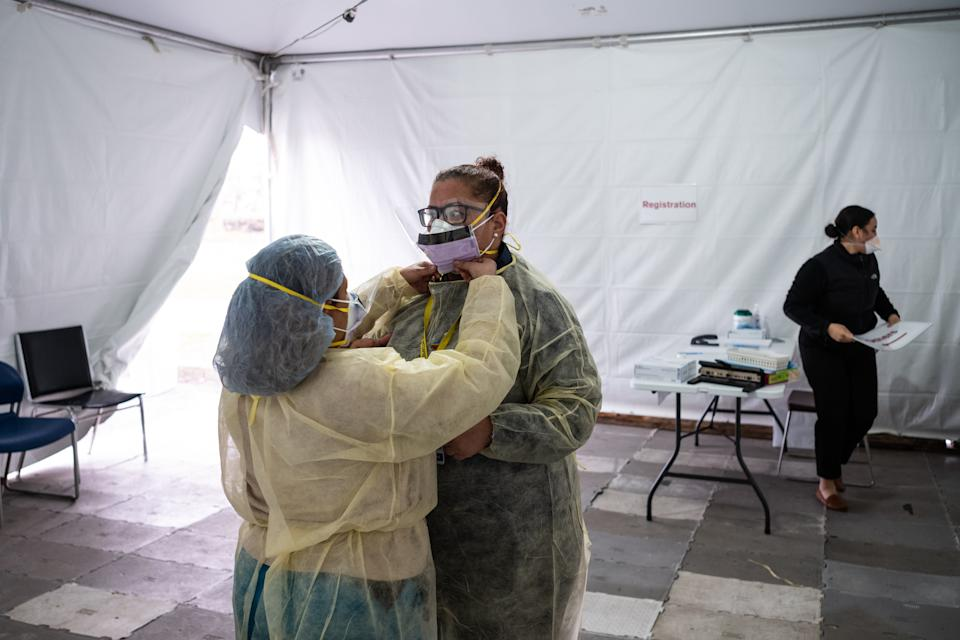 NEW YORK, NY - MARCH 20: Nurses adjust protective masks inside a testing tent at St. Barnabas hospital on March 20, 2020 in New York City. St. Barnabas hospital in the Bronx set-up tents to triage possible COVID-19 patients outside before they enter the main Emergency department area. (Photo by Misha Friedman/Getty Images)