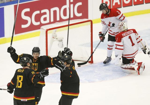 Germany's Janik Moser (L) celebrates his goal on Canada's goalie Jake Paterson (R) with teammates Kai Herpich and Dominik Kahun (2nd L) as Canada's Adam Pelech removes the puck from the net during the first period of their IIHF World Junior Championship ice hockey game in Malmo, Sweden, December 26, 2013. REUTERS/Alexander Demianchuk (SWEDEN - Tags: SPORT ICE HOCKEY)