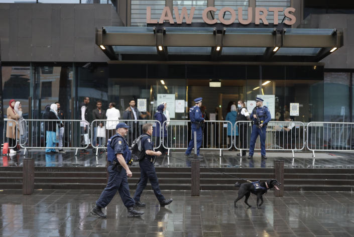 A police dog handler and his colleagues patrol outside the Christchurch High Court as family and survivors from the March 2019 Christchurch mosque shootings arrive for the sentencing of twenty-nine-year-old Australian Brenton Harrison Tarrant, in Christchurch, New Zealand, Monday, Aug. 24, 2020. Tarrant has pleaded guilty to 51 counts of murder, 40 counts of attempted murder and one count of terrorism in the worst atrocity in the nation's modern history. (AP Photo/Mark Baker)