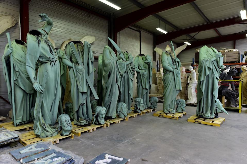 A picture taken in Marsac-sur-Isle near Bordeaux, on April 16, 2019 shows statues which sat around the spire of the Notre-Dame cathedral in Paris, stored in SOCRA workshop before restoration. - Paris was struck in its very heart as flames devoured the roof of Notre-Dame cathedral, causing a spire to collapse and raising fears over the future of the nearly millenium old building and its precious artworks. The sixteen statues which sitted around the spire of the cathedral, 12 apostles and the 4 evangelists commisioned in the 1860s during the great restoration of the cathedral by Viollet-le-Duc, have been removed in April to be sent in southwest France for restoration. (Photo by GEORGES GOBET / AFP)        (Photo credit should read GEORGES GOBET/AFP/Getty Images)