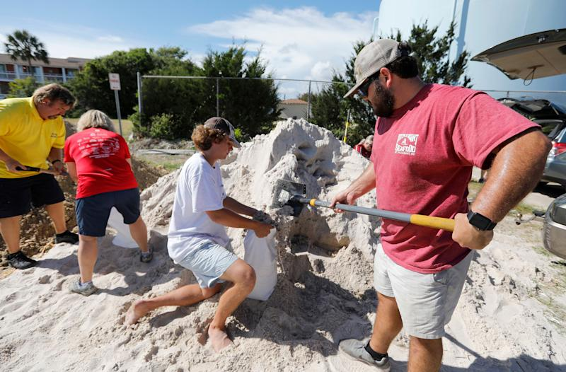 Walker Townsend, at right, from the Isle of Palms, South Carolina, fills a sandbag while Dalton Trout, in center, holds the bag at the Isle of Palms municipal lot on Monday, Sept. 10.