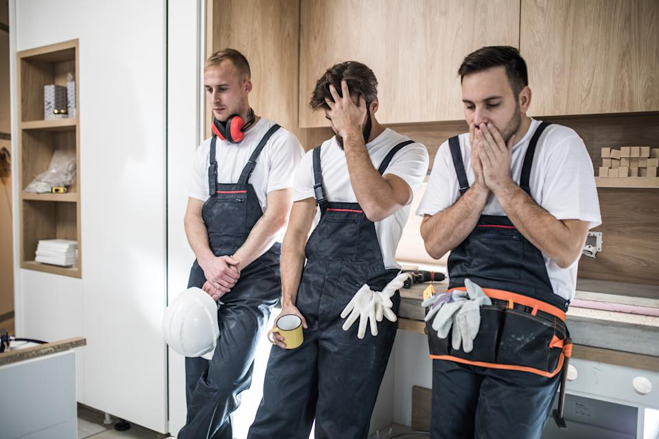 Group of young construction workers having problems during home renovation process.