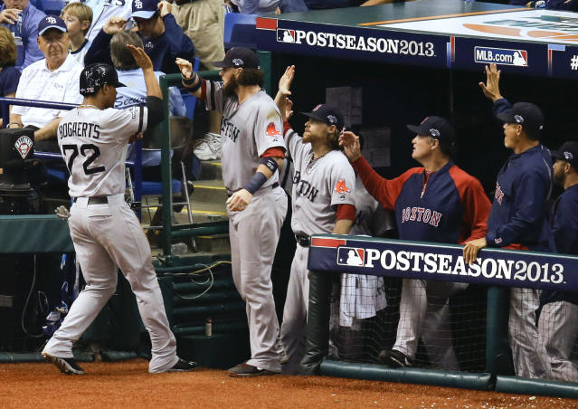 Boston Red Sox's Xander Bogaerts (72) trades high-fives with teammates in the dugout after scored in the seventh inning on a wild pitch by Tampa Bay Rays relief pitcher Joel Peralta in Game 4 of baseball's American League division series, Tuesday, Oct. 8, 2013, in St. Petersburg, Fla. (AP Photo/John Raoux)