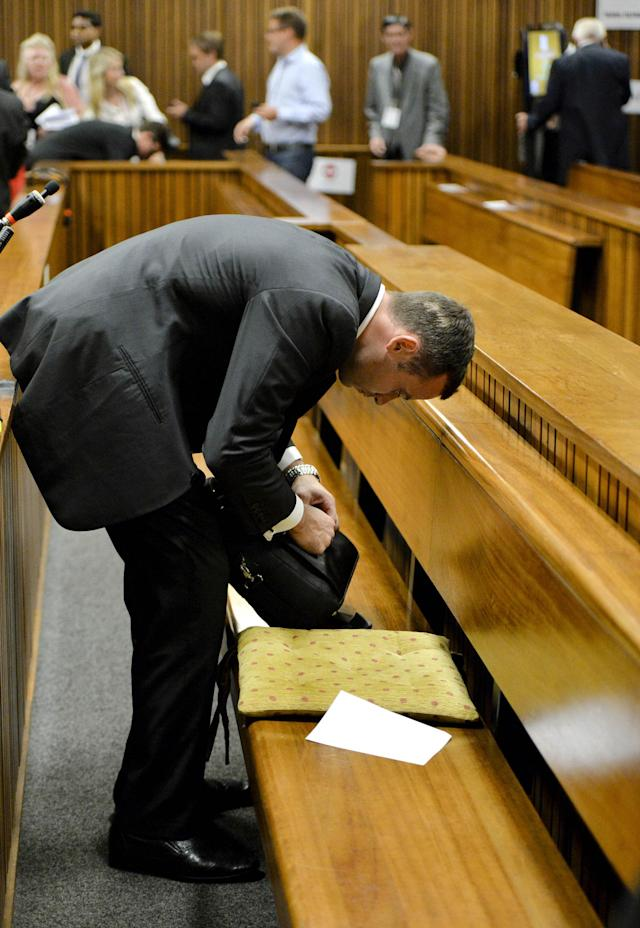 Oscar Pistorius packs up documents for a lunch break in the high court in Pretoria, South Africa, Monday, March 3, 2014. Pistorius is charged with murder with premeditation in the shooting death of girlfriend Reeva Steenkamp in the pre-dawn hours of Valentine's Day 2013. (AP Photo/Herman Verwey, Pool)