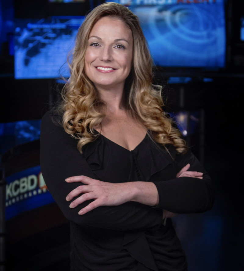 Kelly Plasker folds her arms and poses for a professional photo shoot in a TV studio.