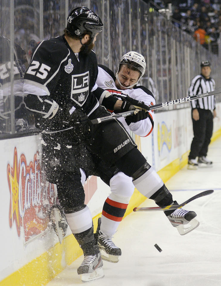 Los Angeles Kings left wing Dustin Penner (25) collides with New Jersey Devils defenseman Marek Zidlicky (2) in the first period during Game 3 of the NHL hockey Stanley Cup finals, Monday, June 4, 2012, in Los Angeles. (AP Photo/Mark J. Terrill)