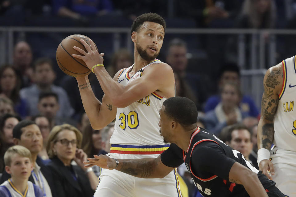 Golden State Warriors guard Stephen Curry (30) looks to pass over Toronto Raptors guard Norman Powell during the first half of an NBA basketball game in San Francisco, Thursday, March 5, 2020. (AP Photo/Jeff Chiu)