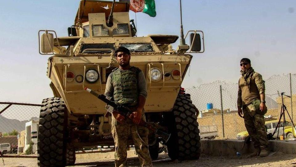 Afghan secuirity forces sit at a checkpoint near the border with Pakistan