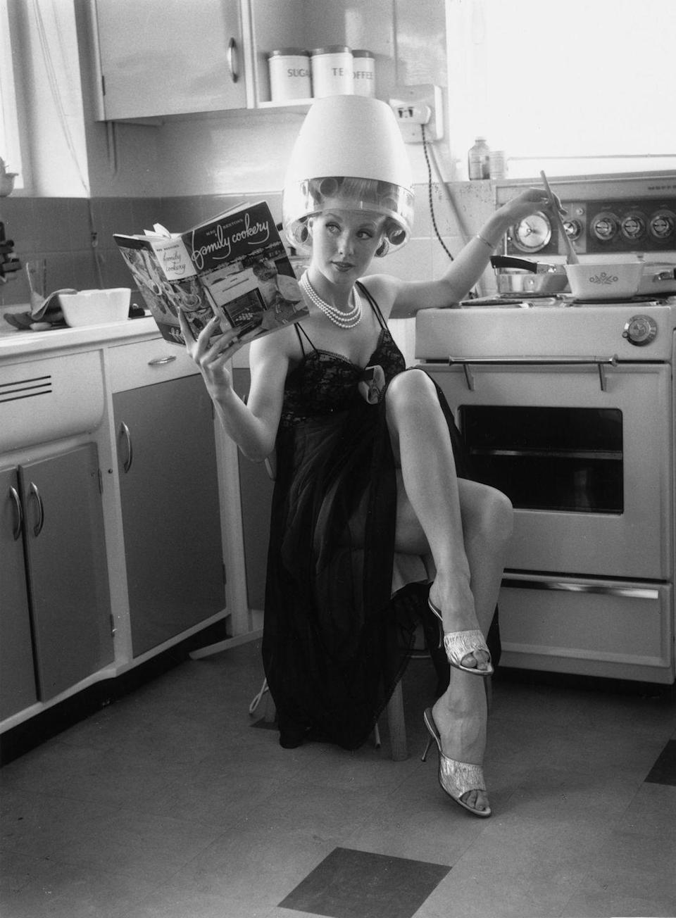 <p>Actress Barbara Roscoe demonstrates her multitasking skills at home in 1963, as she mans the stove while drying her hair. </p>