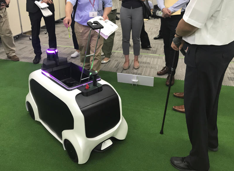 """In this Thursday, July 18, 2019, photo, a """"field support robot"""" is demonstrated before the media at Toyota Motor Corp. headquarters in Tokyo. The Japanese automaker Toyota, a major Olympic sponsor, is readying various robots for next year's Tokyo Olympics, including the one which has intelligence to avoid obstacles in its path and helps bring back thrown objects like javelins and discuses. (AP Photo/Yuri Kageyama)"""