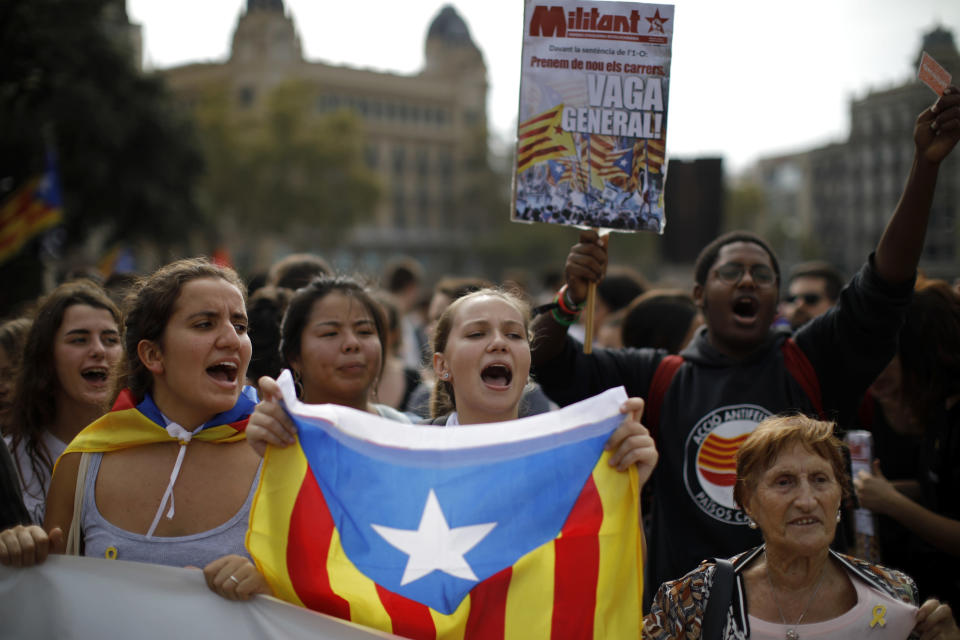 People wearing yellow ribbons in support of jailed pro-independence politicians and carrying Estelada pro-independence flags protest in Barcelona, Spain, Monday, Oct. 14, 2019. Spain's Supreme Court on Monday convicted 12 former Catalan politicians and activists for their roles in a secession bid in 2017, a ruling that immediately inflamed independence supporters in the wealthy northeastern region. Poster reads in Catalan, General Strike. (AP Photo/Emilio Morenatti)