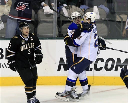 St. Louis Blues left wing David Perron (57) and St. Louis Blues center Patrik Berglund (21), of Sweden, embrace as Dallas Stars defenseman Stephane Robidas (3) skates away after Perron scored a goal during the second period of an NHL hockey game on Saturday, Jan. 26, 2013, in Dallas. (AP Photo/John F. Rhodes)