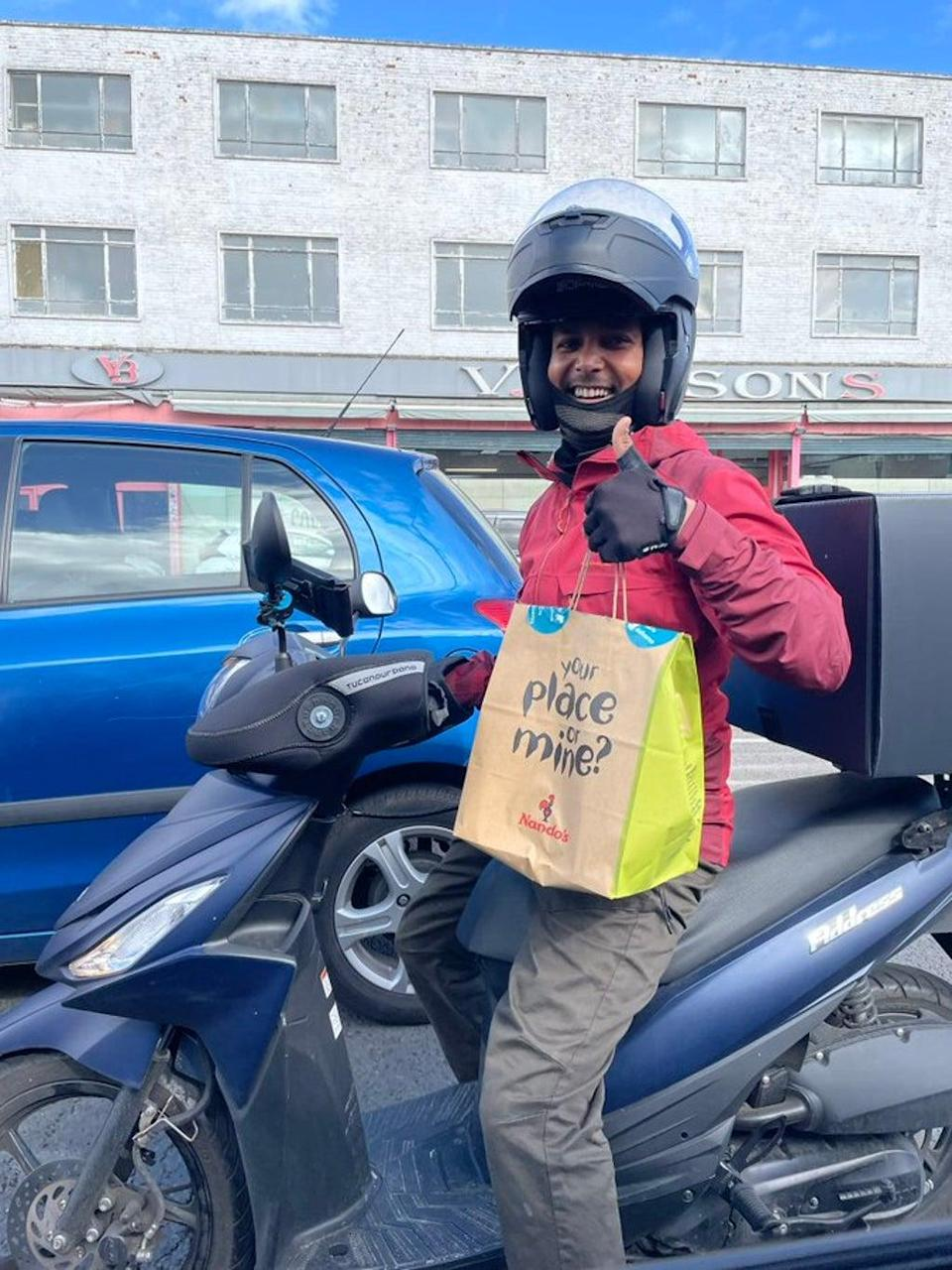 A delivery rider arriving at a petrol station with a takeaway order (Twitter/ Lily Potkin)
