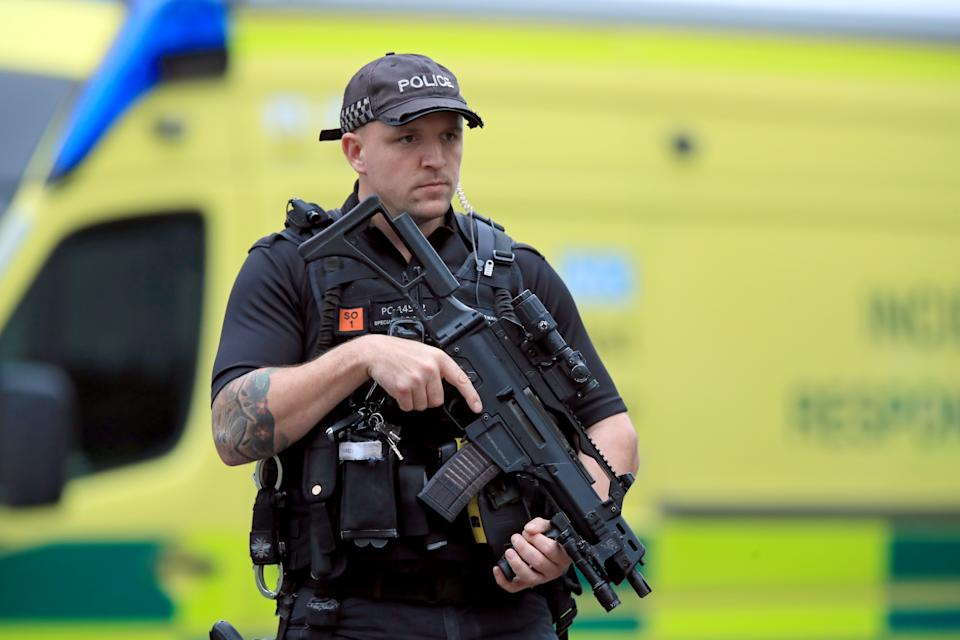 An armed police officer outside the Arndale Centre in Manchester where at least five people have been treated after a stabbing incident.