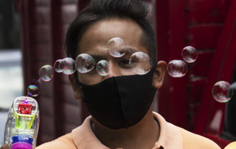 Martin Santiaguillo hawks bubble toy guns along the iconic Reforma Avenue in Mexico City, Friday, Aug. 14, 2020, amid the new coronavirus pandemic. (AP Photo/Marco Ugarte)
