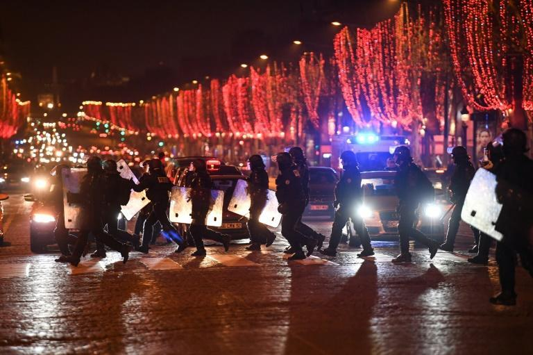 Riot police officers cross the Champs-Elysees in Paris which has been a focal point for the yellow vest protests