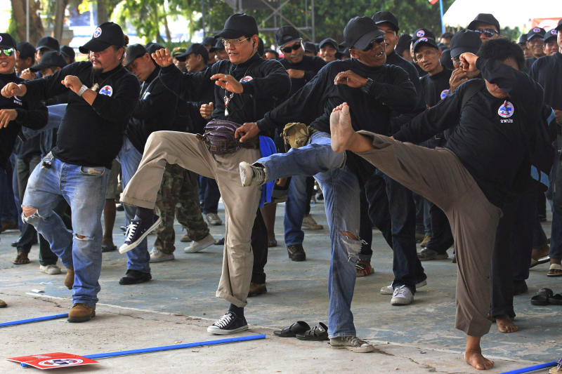 """In this April 3, 2014 photo, black-clad supporters of Thai Prime Minister Yingluck Shinawatra perform in a Thai kickboxing exercise in Udon Thani province, Thailand. Following the directions of a trainer on a nearby stage, they fended off kicks and practiced footwork to loud speakers blaring music typically heard at a Thai kickboxing stadium. It was was part of a two-day training course for farmers, laborers and others in the heart of pro-government """"Red Shirt"""" country - Thailand's rural, poor north and northeast. (AP Photo/Sakchai Lalit)"""