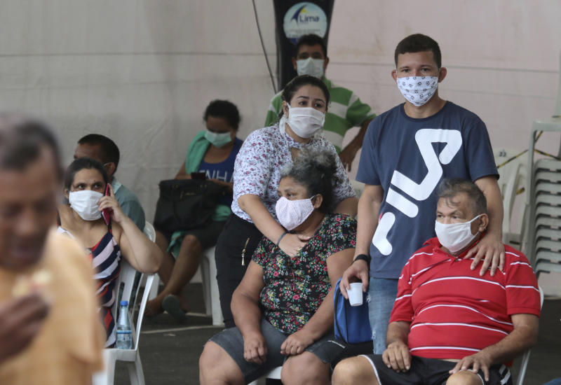 In this April 16, 2020 photo, people suspected of suffering from COVID-19 disease, wait for medical attention outside the 28 de Agosto hospital in Manaus, Amazonas state, Brazil. Manaus' health care system, already strained before the coronavirus crisis, is buckling under the current onslaught of coronavirus patients. (AP Photo/Edmar Barros)